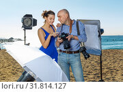 Photographer and model discussing picture on camera display during photo session on seaside in sunny day. Стоковое фото, фотограф Яков Филимонов / Фотобанк Лори