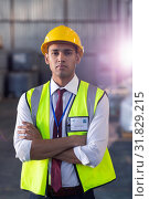 Купить «Male staff in hardhat and reflective jacket standing with arms crossed in warehouse», фото № 31829215, снято 23 марта 2019 г. (c) Wavebreak Media / Фотобанк Лори