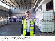 Купить «Mature female staff in reflective jacket standing in warehouse», фото № 31829223, снято 23 марта 2019 г. (c) Wavebreak Media / Фотобанк Лори