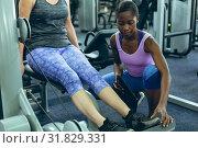 Купить «Female trainer assisting active senior woman to work out on leg curl machine», фото № 31829331, снято 24 марта 2019 г. (c) Wavebreak Media / Фотобанк Лори