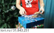Купить «Women's hands are laying Christmas toys on gift boxes», видеоролик № 31843251, снято 25 ноября 2018 г. (c) Aleksandr Sulimov / Фотобанк Лори