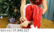 Купить «Mother puts her son on the head with a new year hat for Santa Claus», видеоролик № 31843327, снято 25 ноября 2018 г. (c) Aleksandr Sulimov / Фотобанк Лори
