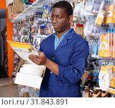 Купить «Confident African-American handyman choosing materials for overhauls in household store», фото № 31843891, снято 21 января 2019 г. (c) Яков Филимонов / Фотобанк Лори