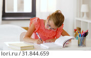Купить «student girl with book writing to notebook at home», видеоролик № 31844659, снято 21 июля 2019 г. (c) Syda Productions / Фотобанк Лори
