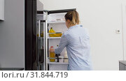 Купить «woman taking juice from fridge at home kitchen», видеоролик № 31844719, снято 21 июля 2019 г. (c) Syda Productions / Фотобанк Лори