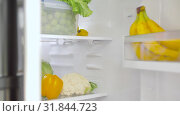 Купить «hand opening fridge with vegetables at kitchen», видеоролик № 31844723, снято 21 июля 2019 г. (c) Syda Productions / Фотобанк Лори
