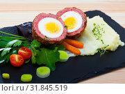 Купить «Dishes of traditional Scottish cuisine of scotch egg served with greens and potatoes», фото № 31845519, снято 6 июня 2020 г. (c) Яков Филимонов / Фотобанк Лори