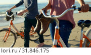 Купить «Couple with bicycle walking on the beach 4k», видеоролик № 31846175, снято 10 сентября 2018 г. (c) Wavebreak Media / Фотобанк Лори