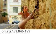Купить «Young ballerina stretching her leg while dancing in the city 4k», видеоролик № 31846199, снято 26 сентября 2018 г. (c) Wavebreak Media / Фотобанк Лори