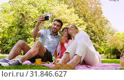 Купить «family having picnic and taking selfie at park», видеоролик № 31846627, снято 21 июля 2019 г. (c) Syda Productions / Фотобанк Лори