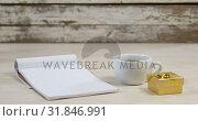 Купить «Notepad, cup of black coffee and golden gift box on wooden surface 4k», видеоролик № 31846991, снято 11 октября 2018 г. (c) Wavebreak Media / Фотобанк Лори