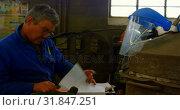Купить «Male worker writing on clipboard in foundry workshop 4k», видеоролик № 31847251, снято 27 сентября 2018 г. (c) Wavebreak Media / Фотобанк Лори