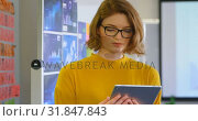 Купить «Front view of young female executive working on digital tablet in modern office 4k», видеоролик № 31847843, снято 29 сентября 2018 г. (c) Wavebreak Media / Фотобанк Лори