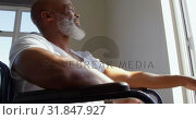 Купить «Low angle view of mature black handicap man sitting on wheelchair near the window at home 4k», видеоролик № 31847927, снято 7 ноября 2018 г. (c) Wavebreak Media / Фотобанк Лори