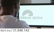 Купить «Rear view of black male executive working on computer at desk in office 4k», видеоролик № 31848143, снято 29 сентября 2018 г. (c) Wavebreak Media / Фотобанк Лори