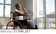 Купить «Side view of mature black handicap man sitting on wheelchair near the window at home 4k», видеоролик № 31848267, снято 7 ноября 2018 г. (c) Wavebreak Media / Фотобанк Лори