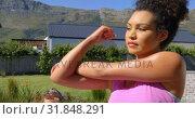 Купить «Front view of young pretty mixed-race woman exercising in backyard of home 4k», видеоролик № 31848291, снято 7 ноября 2018 г. (c) Wavebreak Media / Фотобанк Лори