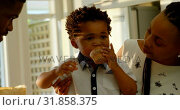 Front view of cute little black son eating cupcake in kitchen of comfortable home 4k. Стоковое видео, агентство Wavebreak Media / Фотобанк Лори