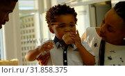 Купить «Front view of cute little black son eating cupcake in kitchen of comfortable home 4k», видеоролик № 31858375, снято 19 октября 2018 г. (c) Wavebreak Media / Фотобанк Лори