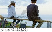 Купить «Rear view of young caucasian skateboarder with skateboard sitting on railing at observation point 4k», видеоролик № 31858551, снято 16 октября 2018 г. (c) Wavebreak Media / Фотобанк Лори