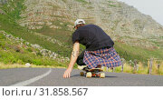 Купить «Rear view of cool young man riding on skateboard on downhill at countryside road 4k», видеоролик № 31858567, снято 16 октября 2018 г. (c) Wavebreak Media / Фотобанк Лори