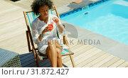 Купить «Fron view of young mixed frace woman relaxing on sun lounger in the backyard of home 4k», видеоролик № 31872427, снято 7 ноября 2018 г. (c) Wavebreak Media / Фотобанк Лори