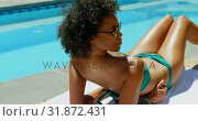 Купить «Young black woman relaxing near swimming pool 4k», видеоролик № 31872431, снято 7 ноября 2018 г. (c) Wavebreak Media / Фотобанк Лори