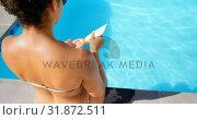 Купить «High angle view of young mixed-race woman applying sunscreen on her shoulder near pool 4k», видеоролик № 31872511, снято 7 ноября 2018 г. (c) Wavebreak Media / Фотобанк Лори