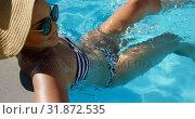 Купить «High angle view of young mixed-race woman relaxing in swimming pool on a sunny day 4k», видеоролик № 31872535, снято 7 ноября 2018 г. (c) Wavebreak Media / Фотобанк Лори