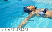 Купить «Close-up of young mixed-race woman floating in swimming pool on a sunny day 4k», видеоролик № 31872543, снято 7 ноября 2018 г. (c) Wavebreak Media / Фотобанк Лори