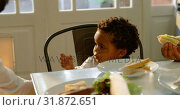 Купить «Front view of cute little black son eating food at dinning table in kitchen of comfortable home 4k», видеоролик № 31872651, снято 19 октября 2018 г. (c) Wavebreak Media / Фотобанк Лори