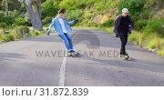 Купить «Front view of cool young caucasian skateboarders skating on downhill at countryside road 4k», видеоролик № 31872839, снято 16 октября 2018 г. (c) Wavebreak Media / Фотобанк Лори