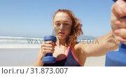 Купить «Woman exercising with dumbbells at beach 4k», видеоролик № 31873007, снято 14 ноября 2018 г. (c) Wavebreak Media / Фотобанк Лори