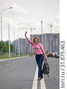 Купить «Hitchhiker waving hands for car stop, attractive mature woman with backpack standing on roadside», фото № 31879463, снято 21 июня 2019 г. (c) Кекяляйнен Андрей / Фотобанк Лори