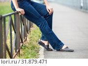 Unrecognizable female sitting on steel fence of pedestrian pathway, blue jeans and comfortable shoes. Стоковое фото, фотограф Кекяляйнен Андрей / Фотобанк Лори
