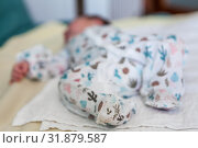 Unrecognizable newborn infant lying in crib dressed creepers, close up view at legs. Стоковое фото, фотограф Кекяляйнен Андрей / Фотобанк Лори