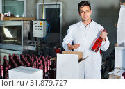 Купить «Man standing in packing section on winemaking factory», фото № 31879727, снято 21 сентября 2016 г. (c) Яков Филимонов / Фотобанк Лори