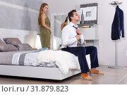 Купить «Man sitting on bed and dressing», фото № 31879823, снято 24 сентября 2018 г. (c) Яков Филимонов / Фотобанк Лори
