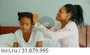 Купить «Side view of mid adult black mother dressing daughters hair on bed in a comfortable home 4k», видеоролик № 31879995, снято 7 ноября 2018 г. (c) Wavebreak Media / Фотобанк Лори
