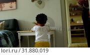 Купить «Rear view of little black boy playing in a comfortable home 4k», видеоролик № 31880019, снято 19 октября 2018 г. (c) Wavebreak Media / Фотобанк Лори