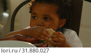 Купить «Close-up of cute little black son eating food at dinning table in kitchen of comfortable home 4k», видеоролик № 31880027, снято 19 октября 2018 г. (c) Wavebreak Media / Фотобанк Лори