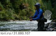 Купить «Side view of caucasian young fisherman fishing in the forest stream on a bright sunny day 4k», видеоролик № 31880107, снято 19 сентября 2018 г. (c) Wavebreak Media / Фотобанк Лори