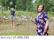 Купить «Aged grandma with her granddaughter playing badminton on backyard at summer season», фото № 31880355, снято 20 июля 2019 г. (c) Кекяляйнен Андрей / Фотобанк Лори