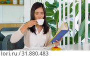 Купить «woman drinking coffee and reading book at cafe», видеоролик № 31880483, снято 21 июля 2019 г. (c) Syda Productions / Фотобанк Лори