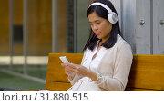 Купить «asian woman with smartphone and headphones», видеоролик № 31880515, снято 21 июля 2019 г. (c) Syda Productions / Фотобанк Лори