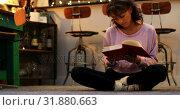 Купить «Front view of mixed-race young woman reading a book in a comfortable home 4k», видеоролик № 31880663, снято 2 октября 2018 г. (c) Wavebreak Media / Фотобанк Лори