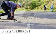 Купить «Front view of cool young caucasian man doing skateboard trick on downhill at countryside road 4k», видеоролик № 31880691, снято 16 октября 2018 г. (c) Wavebreak Media / Фотобанк Лори