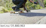 Купить «Side view of cool young caucasian man doing skateboard trick on downhill at countryside road 4k», видеоролик № 31880963, снято 16 октября 2018 г. (c) Wavebreak Media / Фотобанк Лори