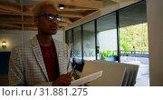 Купить «Front view of young black businessman writing on document in modern office 4k», видеоролик № 31881275, снято 1 октября 2018 г. (c) Wavebreak Media / Фотобанк Лори