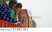 Купить «Side view of young black couple wrapped in American flag and leaning on railing at beach hut 4k», видеоролик № 31881367, снято 14 ноября 2018 г. (c) Wavebreak Media / Фотобанк Лори